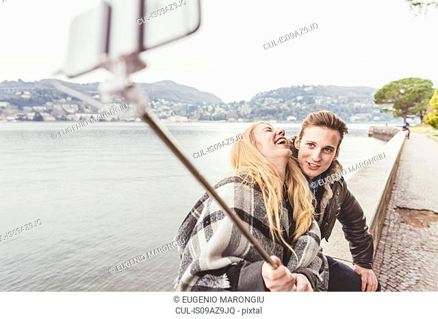 Young couple laughing taking smartphone selfie on harbour wall, Lake Como, Italy