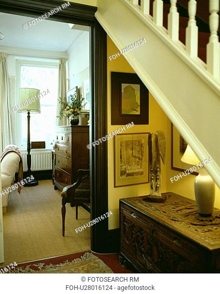 Pictures and carved wooden chest below staircase in small hall with door open to living room