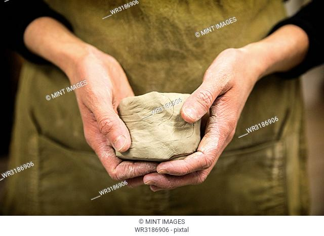 Close up of potter holding piece of pottery clay