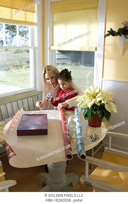 Mother and young daughter wrapping gifts on kitchen table by large windows
