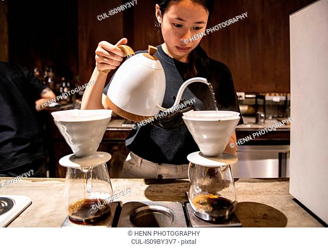 Female barista preparing a drip coffee in independent coffee roaster and cafe, Bangkok