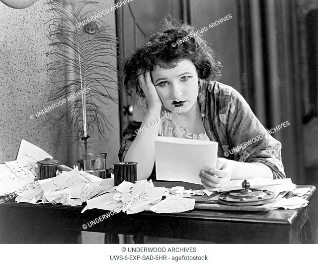 United States: c. 1923.A woman sitting at a desk with her head in her hand, looking depressed with a pile of papers
