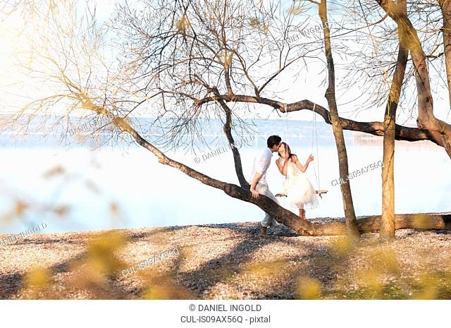 Couple on tree swing by ocean kissing