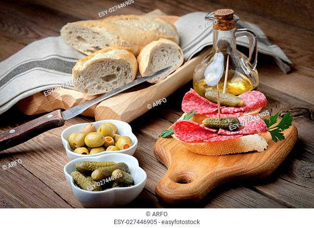 Spanish cuisine. Tapas with sliced salami, olives and cucumber on a wooden table. on a wooden table