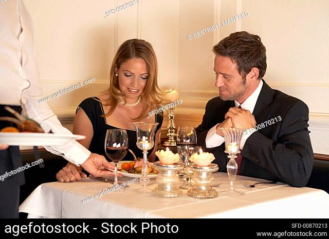 Waiter serving a meal to a young couple