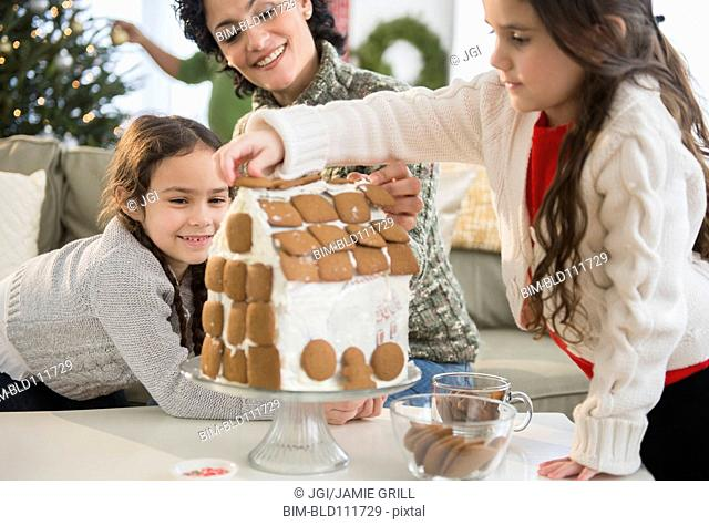 Mother and daughters making gingerbread house
