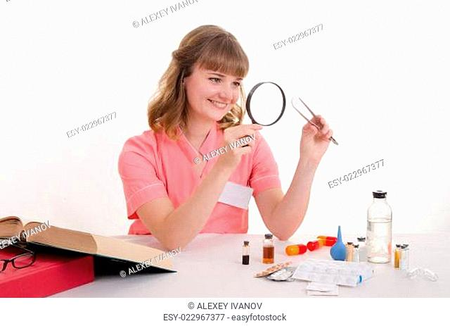 Student pharmacist considers the pill under magnifying glass