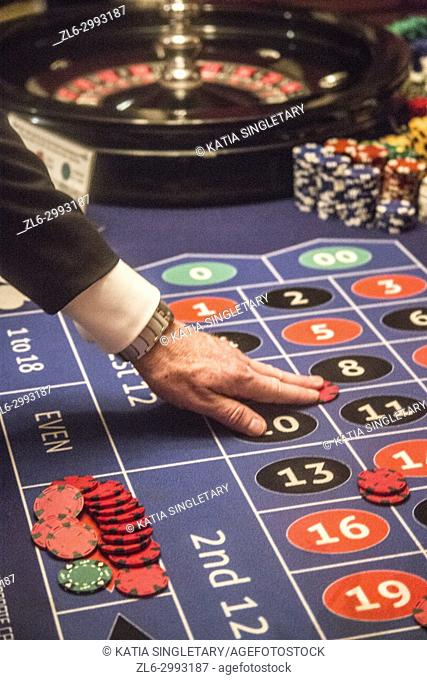Playing roulette, This gentleman is betting money with his chips. He is playing the chips on the numbers he wants to bet on