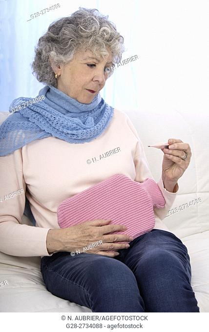 Senior woman feeling unwell, at home holding a hot water bottle on her stomach, and a medical thermometer in one hand, with a blue scarf around her neck