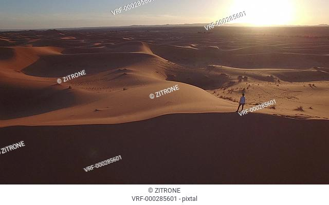 Drone footage of woman standing on sand dune at Erg Chebbi, Morocco