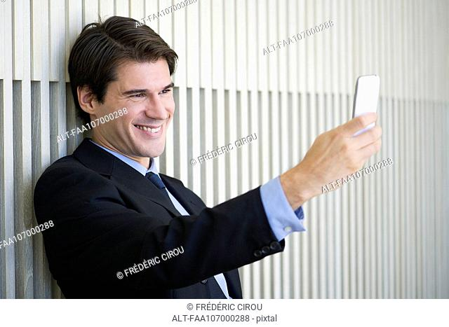 Businessman using smartphone to take a selfie