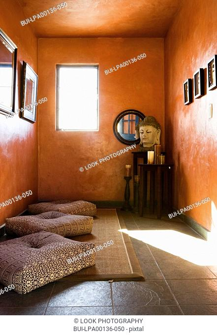 Small clean yoga room with burnt orange walls