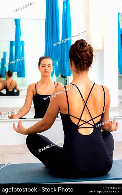 Rear view of young woman sitting in front of mirror meditating. Girl with eyes closed reflected in mirror