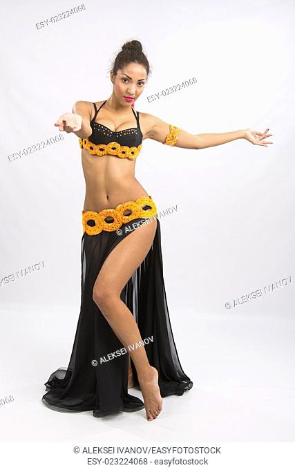 Young girl mulatto dancing in a long black candid open dress, is isolated on a light background