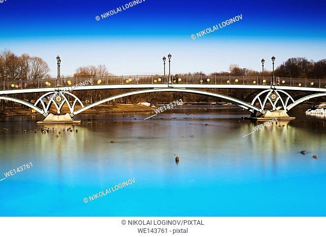 Horizontal dramatic arc bridge in Moscow park background