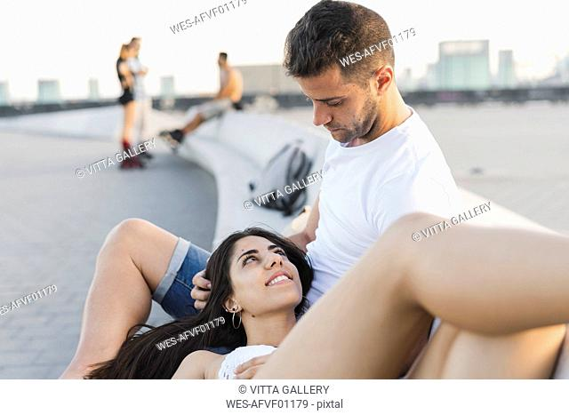 Happy young woman lying on lap of her boyfriend, portrait