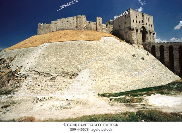 Great Citadel of Aleppo with the glacis defensive mound in the foreground and the monumental gateway and entrance. Halab, Syria