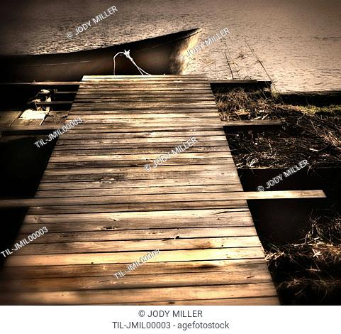 A small boat moored by a small timber jetty