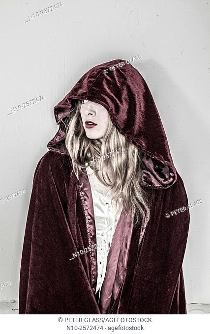 Blonde teenage girl wearing a robe with a hood