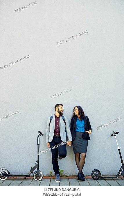 Happy couple with scooters leaning against a wall