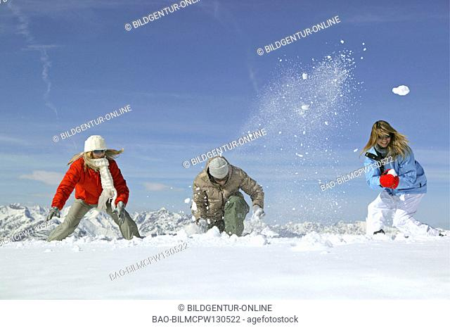 young people having snowball fight fun