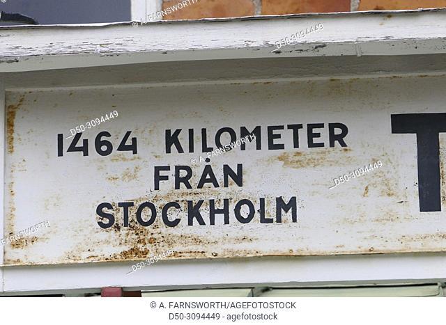 A distance sign (1464 kilometers) on an old train station in Torneträsk. Kiruna, Sweden