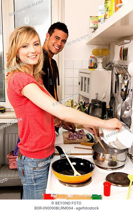 portrait of young couple in kitchen cooking together