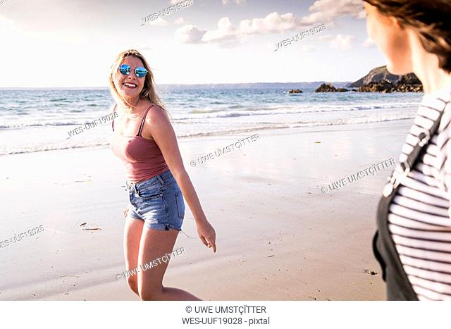Two girlfriends having fun, walking on the beach
