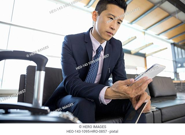 Businessman with cell phone waiting in airport
