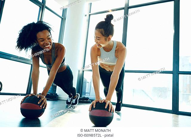 Two young women working out in gym, using gym equipment