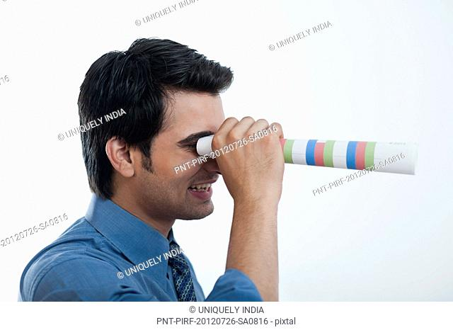 Businessman looking through from a paper binoculars