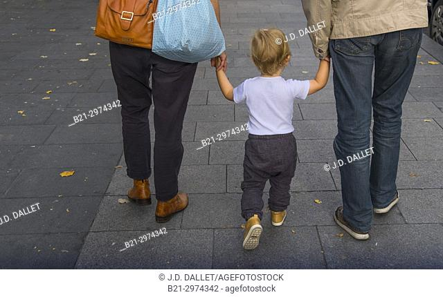 Little child holding hands with mom and dad, walking on the street