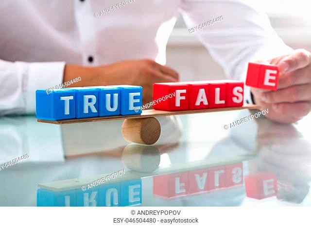 Businessman's hand balancing true and false blocks on wooden seesaw over desk