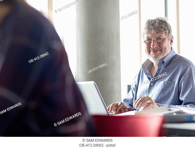 Portrait smiling man working at laptop in adult education classroom