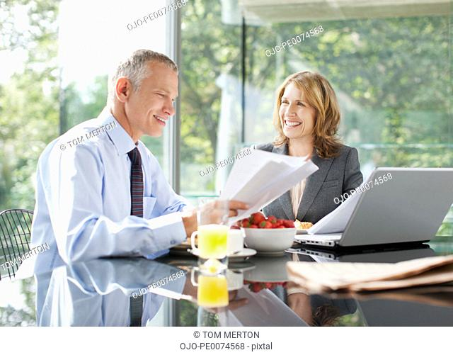 Business people working over breakfast