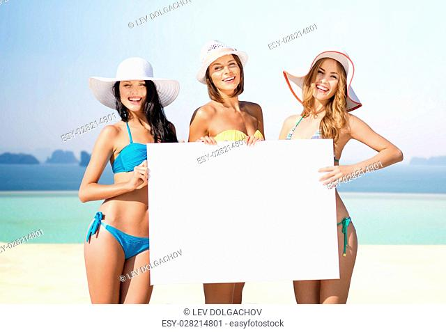 summer holidays, travel, people, advertisement and vacation concept - happy young women in bikinis holding white board over infinity edge pool background
