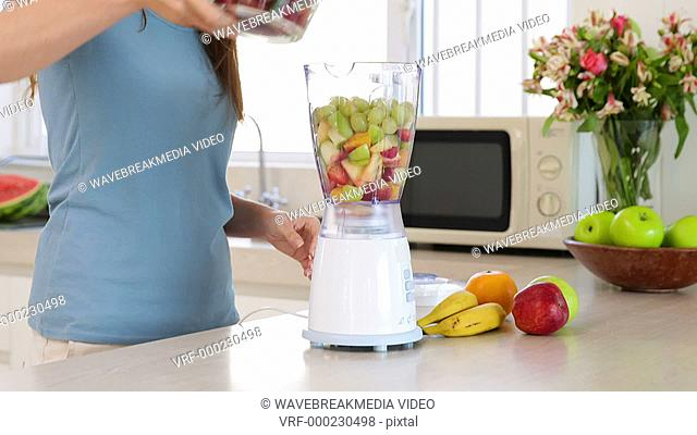 Smiling woman making a smoothie at home in the kitchen