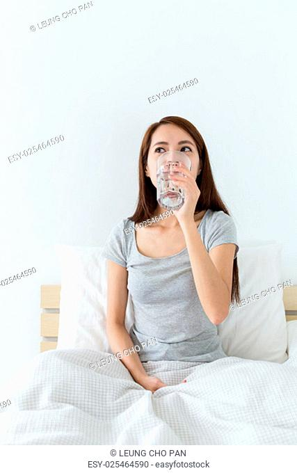 Woman drinking a glass of water at morning