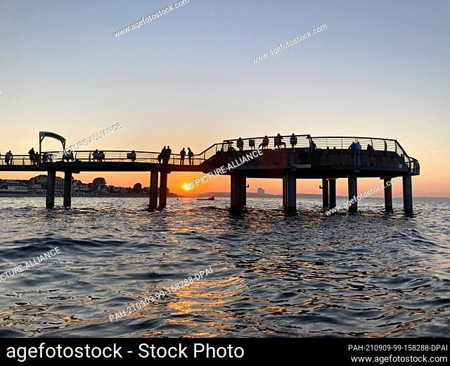 09 September 2021, Schleswig-Holstein, Timmendorfer Strand: Tourists watch a perfect September sunset on a pier in Lübeck Bay
