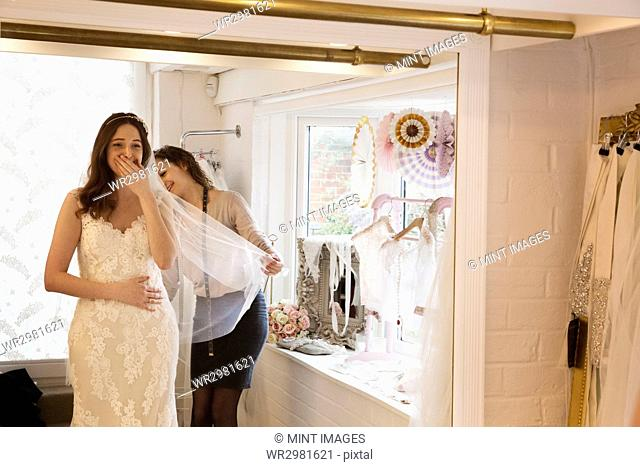 A bride, a young woman trying on a wedding dress with lace overlay and veil, her hand to her face in delight and surprise