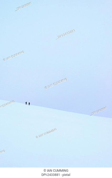 Two people walking along ridge in snow covered, winter conditions on Beinn an Dothaidh, near Bridge of Orchy; Argyll and Bute, Scotland