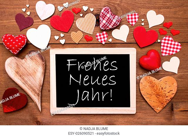 Chalkboard With German Frohes Neues Jahr Means Happy New Year. Many Red Textile Hearts. Wooden Background With Vintage, Rustic Or Retro Style
