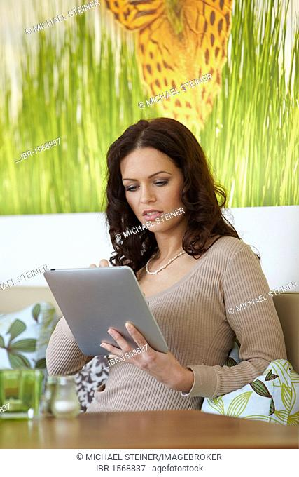 Young woman using an iPad tablet computer at a cafe table