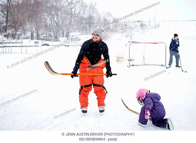 Father and daughter playing ice hockey in winter landscape