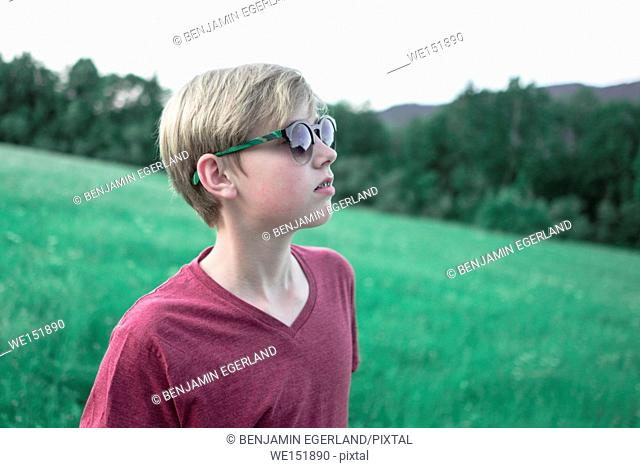 cool teenage boy with sunglasses in nature