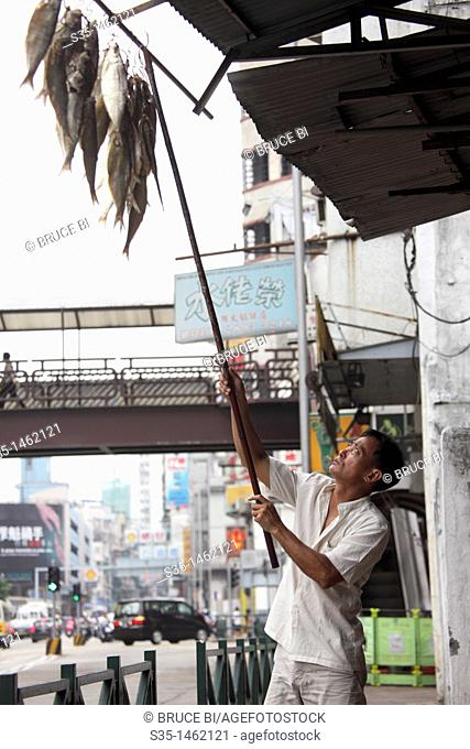 A dried fish seller hanging his goods along sidewalk  Macau  China