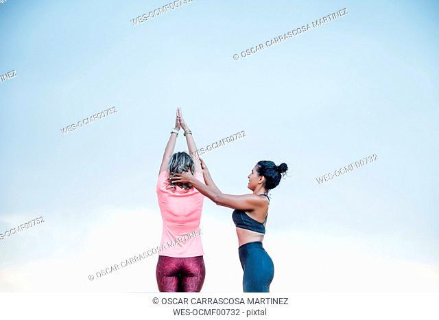 Woman teaching yoga to senior woman