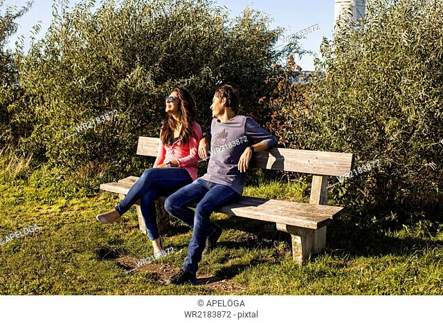 Full length of young couple relaxing on park bench