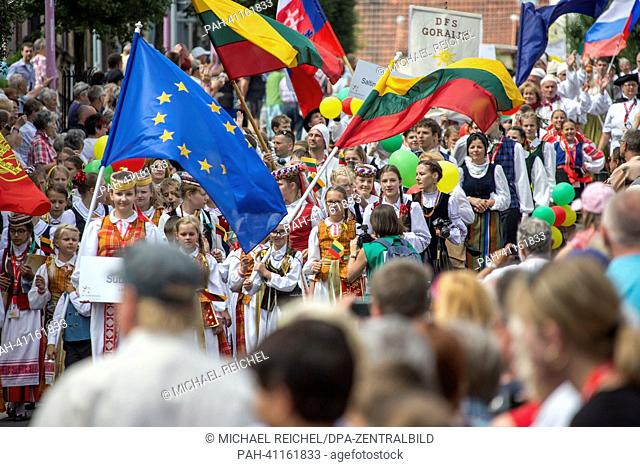 People wearing traditional costume from various European countries walk in the parade through the center of Gotha, Germany, 20 July 2013