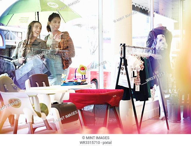 Caucasian women window shopping outside store